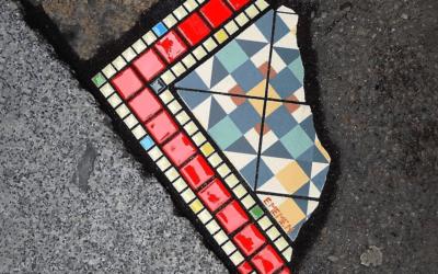 Un artista francese gira per le città riparando le buche con dei mosaici colorati